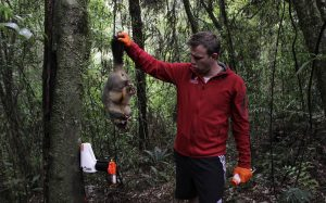 man-holding-dead-possum-next-to-good-nature-trap