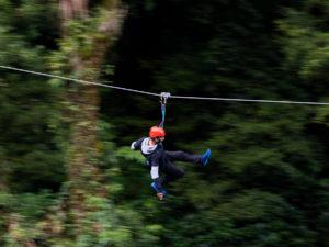 Man-going-fast-down-zipline-through-forest