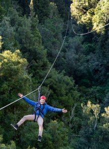 Manin-blue-jacket-on-zipline-above-forest